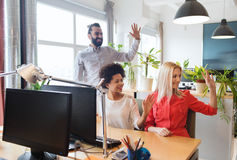 Happy creative team waving hands in office. Business, startup and office concept - happy creative team waving hands in office stock photography