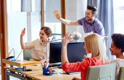 Happy creative team waving hands in office. Business, startup and office concept - happy creative team waving hands in office royalty free stock image