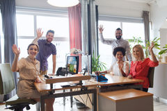Happy creative team waving hands in office. Business, startup and office concept - happy creative team waving hands in office royalty free stock photo