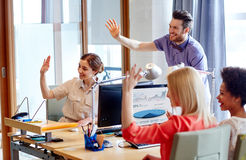 Happy creative team waving hands in office. Business, startup and office concept - happy creative team waving hands in office stock photos