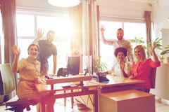 Happy creative team waving hands in office. Business, startup and office concept - happy creative team waving hands in office royalty free stock images
