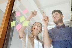 Happy creative team writing on blank office glass stock photos