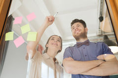 Happy creative team writing on blank office glass Royalty Free Stock Photo