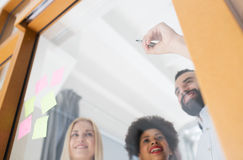 Happy creative team writing on blank office glass Royalty Free Stock Image