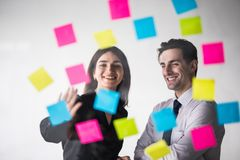 Business, startup, planning, management and people concept - happy creative team writing on stickers at office glass board in mode Stock Images