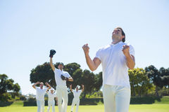 Happy cricket team enjoying victory while standing on field. Against clear sky stock images