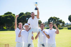 Happy cricket team with throphy standing on field. Against clear sky Royalty Free Stock Photos