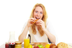 Happy with croissant. Woman in the morning at the breakfast table stock photography