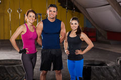 Happy crossfit instructors. Portrait of three good-looking and athletic cross-training instructors ready to begin the workout of the day Stock Photos
