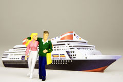 Happy Cruisers. Figurine of a young happy couple in front of a cruise ship Royalty Free Stock Photos