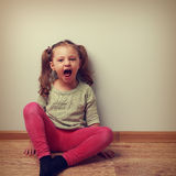 Happy crying kid with open mouth sitting on the floor. Vintage Stock Photography