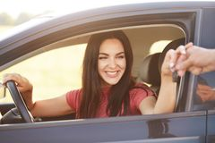 Happy Cuacasian young female takes car key from her husband, recieves expensive gift, going to drive automobile, has broad smile, stock images