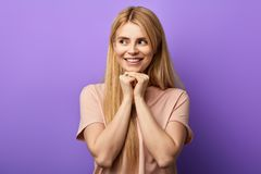 Happy cunning girl with hands on chin, and dreams or thinks. royalty free stock photo