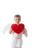 Happy cupid boy with wings holding red plush heart Royalty Free Stock Image