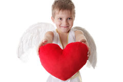 Happy cupid boy with wings holding red plush heart Royalty Free Stock Images