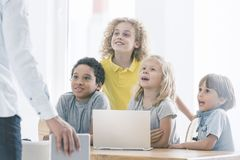 Students admiring computer science teacher. Happy, curious elementary school students admiring their computer science teacher talking about programming royalty free stock photos