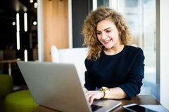 Happy curlu young woman use laptop in modern place with bright windows. Royalty Free Stock Photo