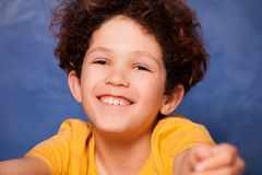 Happy curly boy smiling and looking at camera. Close-up portrait of preteen curly boy smiling and looking at camera Stock Photos