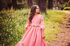 Happy curly child girl in fairytale princess dress dancing in summer forest Royalty Free Stock Photography