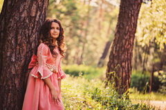 Happy curly child girl in fairytale princess pink dress on the walk in summer forest Stock Photo