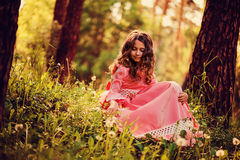Happy curly child girl in pink princess dress on the walk in summer forest Stock Image