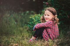 Happy curly child girl in plaid dress sitting on grass in summer day Stock Photos