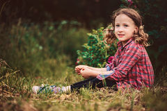 Happy curly child girl in plaid dress sitting on grass in summer day Royalty Free Stock Photos