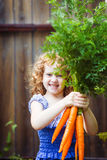 Happy curly girl with bunch of carrots. Stock Images