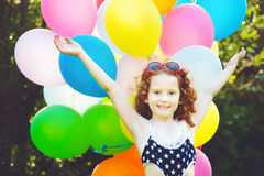 Happy curly girl with colorful balloon in summer park, celebrati Royalty Free Stock Photography
