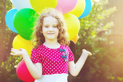 Happy curly girl with colorful balloon in summer park. Toning to Stock Photography