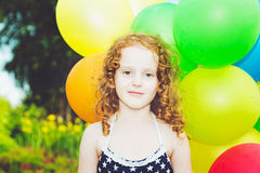 Happy curly girl with colorful balloon in summer park. Toning to Stock Photos