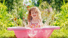 Happy curly girl taking water procedures in summer garden. Royalty Free Stock Photos