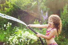 Happy curly girl under water splashes in the summer garden. Royalty Free Stock Photos