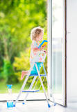 Happy curly girl washing a window in white room Stock Photo