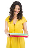Happy curly haired brunette holding notebooks Stock Photography