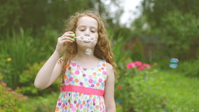 Happy curly haired girl blowing soap bubbles in summer park. Slow motion stock footage