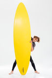 Happy curly sportsman holding surfboard Stock Images