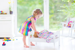 Happy curly toddler girl playing with her teddy bear Stock Photography