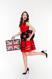 Happy curly woman running with vintage suitcase and vinyl disks Stock Images