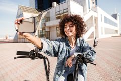 Happy curly woman sitting on modern motorbike outdoors Royalty Free Stock Photography