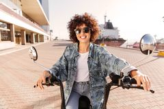 Happy curly woman in sunglasses rides on modern motorbike Stock Photography