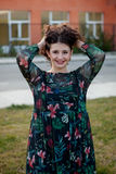 Happy curvy girl with curly hair in the street touching her hair Royalty Free Stock Images