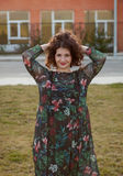 Happy curvy girl with curly hair in the street touching her hair Stock Photos