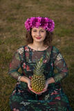 Happy curvy girl with a pineapple and a flower crown. In the landscape Stock Photography