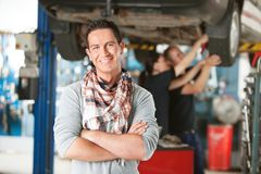 Happy Customer in Auto RepairShop. Portrait of a male happy customer in an auto repair shop with mechanics in background Stock Photos