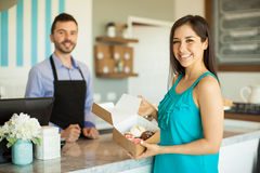 Happy customer in a cake shop. Portrait of a beautiful young women holding a box of cupcakes she just bought in a cake shop and smiling royalty free stock image