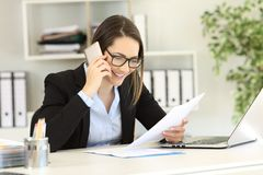 Happy customer calling support service at office. Happy customer calling support service about a paper document at office Stock Photos