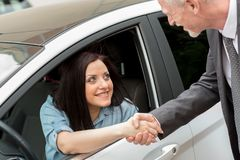 Customer and car salesman shaking hands. Happy customer and car salesman shaking hands Royalty Free Stock Image