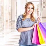Happy customer. With colourful paper bag in great mall, attractive girl enjoying shopping, buying gifts, spending money concept stock image