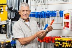 Happy Customer Comparing Screwdrivers In Hardware. Portrait of happy senior customer comparing screwdrivers in hardware shop Royalty Free Stock Image